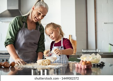 Little cute girl adding milk in dough. Granddaughter with old grandmother measuring milk for cookie dough. Focused child helping mature grandma in apron to prepare a cake in kitchen.