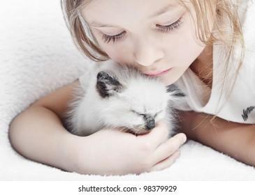 little cute girl affectionately hugging  kitten