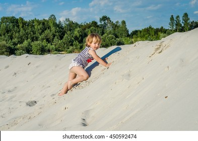 Little cute girl baby child playing in the sand in a T-shirt, shorts and a hat on the sandy beach on a bright hot sunny summer day at the beach at the resort