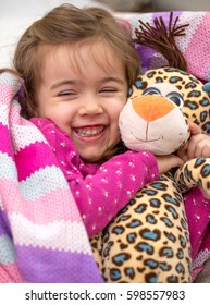 little cute girl in bed with toy tiger,in the pink bed,the concept of childhood and holiday