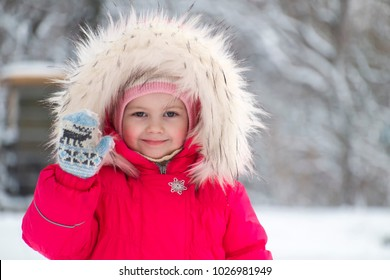 Little cute girl in a big fur hood waving her hand