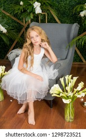 Little cute girl with blond hair in a white dress and white flowers, lilies and orchids on a green background