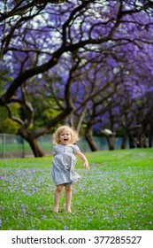 Little cute girl in blue dress is jumping on the grass full of purple flowers under blooming purple trees