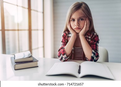 Little cute girl is bored and tired with doing her homework.