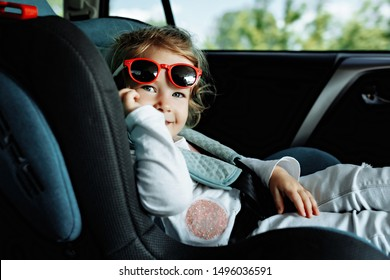 little cute girl in cap sitting in the car in child safety seat and smiling