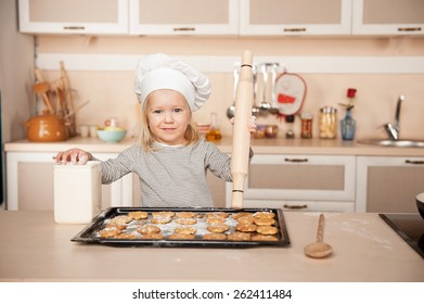Little cute girl with chef hat and rolling pin looking at camera and preparing cookies. Kitchen interior. Concept for young kitchen hands