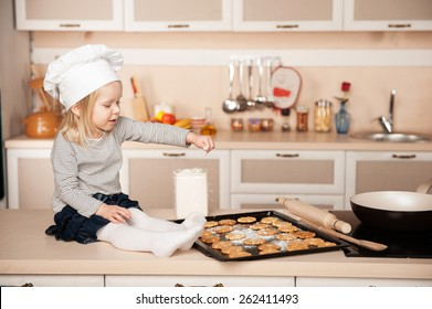 Little cute girl with chef hat preparing cookies. Kitchen interior. Concept for young kitchen hands