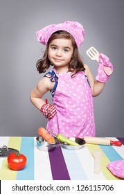 little cute girl with chef uniform posing like a professional model and looking at camera on grey background