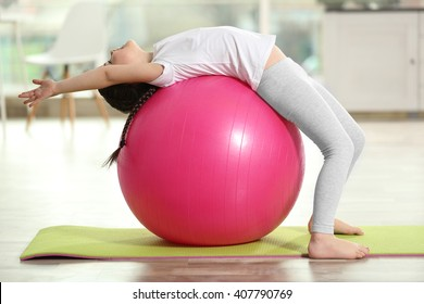 Little cute girl doing exercises with ball on a mat indoor