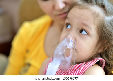 little cute girl doing inhalation at home