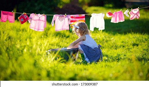 A little cute girl doing the laundry in a small aluminium basin near the clothesline in the meadow on a sunny summer day