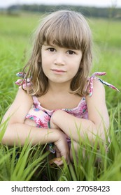 little cute  girl with dried crust sitting in meadow. Summer time