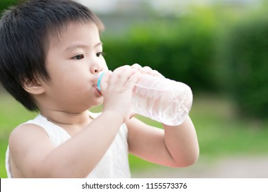 little cute girl drinking clean water from plastic bottle