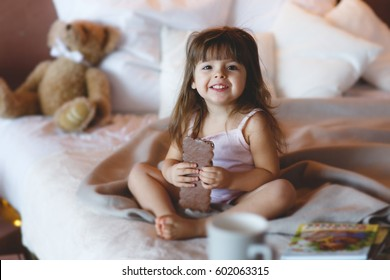 little cute girl eating chocolate bar in bed. smiling child. Little girl with white curly hair in a white lace dress is eating a large bar of chocolate