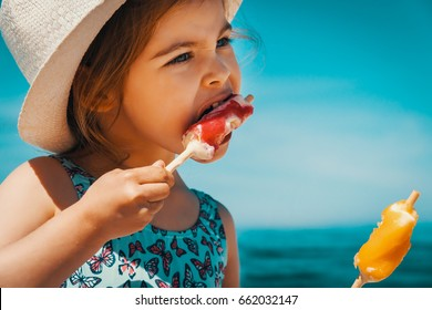 Little and cute girl eating ice cream on the beach on vacation