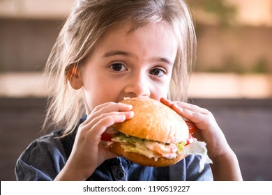 Little cute girl eating a sandwich in a cafe, concept of a children's fast food meal