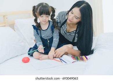 A little cute girl enjoy drawing into the book by colorful pastel with mother on the white bed in the bedroom, education time at home, happy family concept