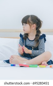 A little cute girl enjoy playing and creating toy by colorful clay with mother on the white bed in the bedroom, education time at home, happy family concept