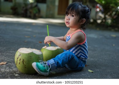 Little cute girl enjoying summer with fresh coconuts. outdoor summer shot.
