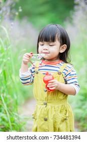 Little cute girl in a flower garden.