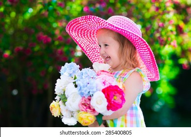 Little cute girl with flowers. Child wearing a pink hat playing in a blooming summer garden. Kids gardening. Children play outdoors. Toddler kid with flower bouquet for birthday or mother's day.