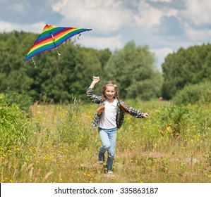 little cute girl flying a kite in a meadow on a sunny day