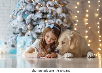 Little cute girl with a golden retriever dog writes letter to Santa near christmas tree