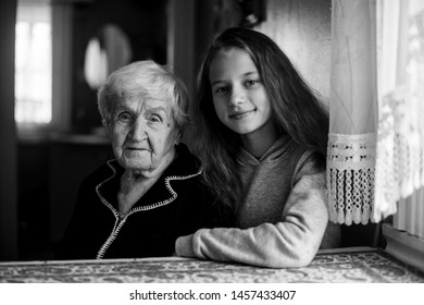 Little cute girl with a grandmother in the house black and white portrait.