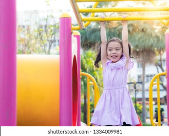 Little cute girl hanging the bar at the park. Fun activity, brain traning and learning skill, exercise