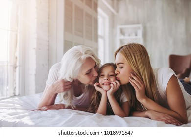 Little cute girl, her attractive young mother and charming grandmother are lying on bed and spending time together at home. Women's generation. International Women's Day. Happy Mother's Day.