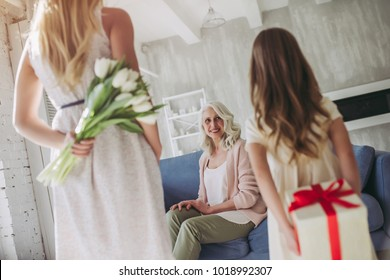 Little cute girl, her attractive young mother and charming grandmother are spending time together at home. Giving presents. Women's generation. International Women's Day. Happy Mother's Day.