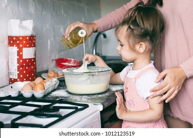 A little cute girl and her mother preparing the dough in the kitchen at home, happy family concept