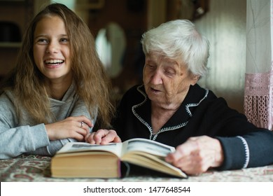 Little cute girl with her old great-grandmother reading a book.