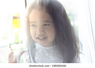 Little cute girl hiding her mother or father for playing hide and seek with her parent. Lovely kid get cheerful and fun behind the curtain at house with laughing, smiling. Beautiful kid is mischievous