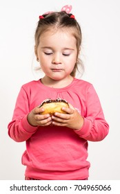 Little cute girl holding donut and posing on camera isolated on white