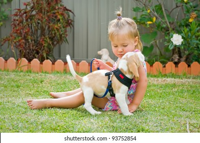 Little cute girl holding a puppy in her arms