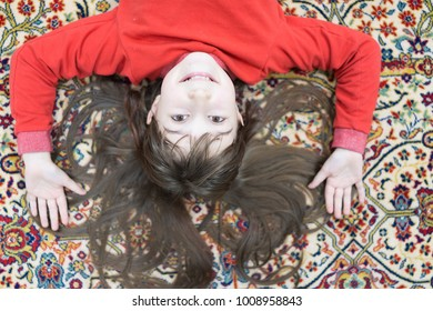 Little cute girl at home on carpet
