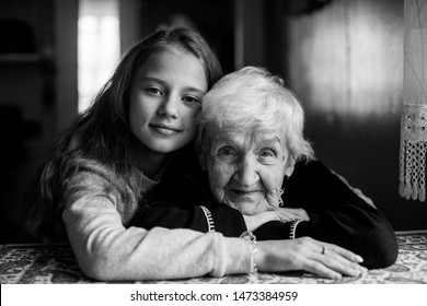 A little cute girl hugs her grandmother. Black and white portrait.