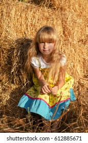 Little cute girl  with long blonde hair in hay