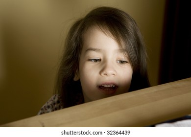 little cute girl looking behind bookshelf