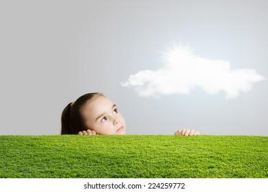 Little cute girl looking at shining sun
