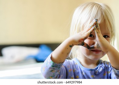 Little cute girl looks through her fingers smeared with paint