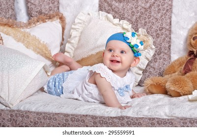 Little cute girl lying in a cradle among the pillows. The concept of carefree childhood.