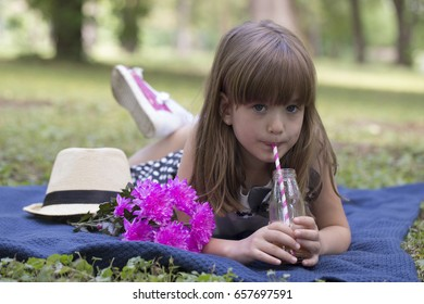 Little cute girl lying on the grass in the park and drinking juice