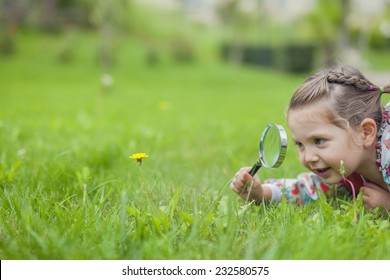 Little cute girl with magnifying glass looking at flower.