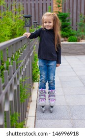 Little cute girl on roller skates in front of her home