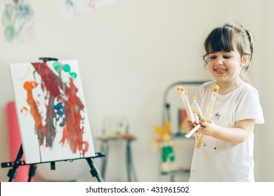 Little cute girl painting  at her home. Selective focus and small depth of field