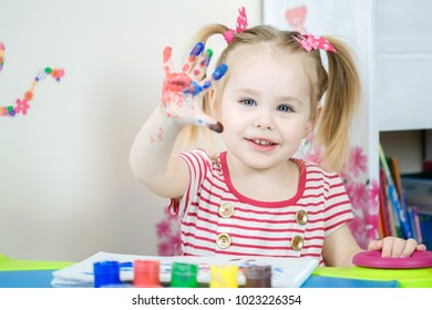 Little cute girl paints with fingers