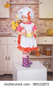 Little cute girl in pink dress and white apron in the kitchen