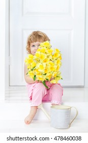Little cute girl in a pink dress sitting on a white rustic porch and hides her face behind a bouquet of yellow garden flowers.